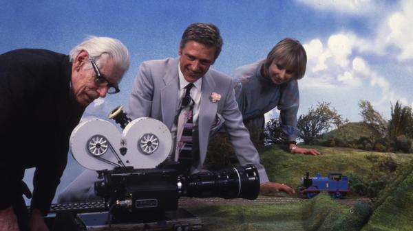 Thomas' creator, Reverend Wilbert Awdry, inspects a setup for the <em>Thomas</em> TV series in 1981. Britt Allcroft, who created the show, is at right.