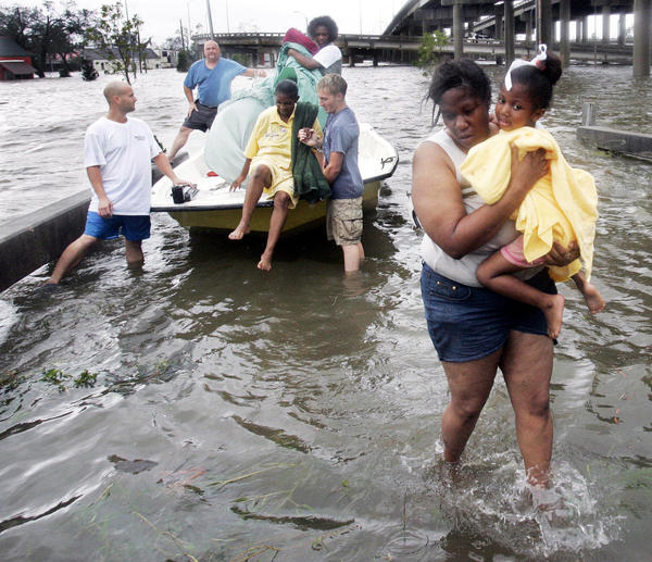 Shante Gruld carries Janeka Garner, 5, to safety after they were rescued from their flooded home by boat in New Orleans on Aug. 29, 2005. The area was flooded after Hurricane Katrina hit the area.