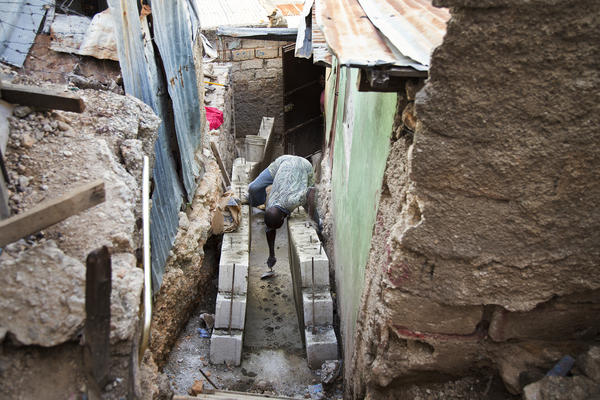 A man works on a pathway in Campeche. As the Red Cross prepares to leave the neighborhood at the end of this year, residents say the hundreds of houses the Red Cross told them would be built do not exist.