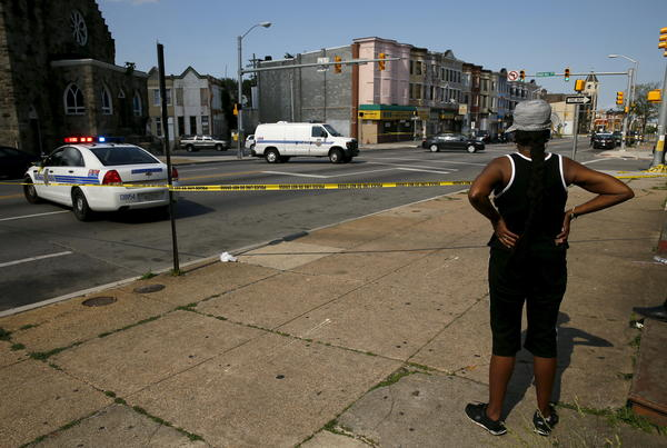 A resident in the neighborhood where Freddie Gray was arrested and where residents rioted over his death in April looks on at the scene of a shooting at the intersection of West North Avenue and Druid Hill Avenue in West Baltimore, Md., on May 30.