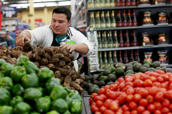 Wal-Mart employee Dayngel Fernandez stocks shelves in the produce department of a Miami store in February. Activists say the company's recent corporate policy changes don't address systemic labor and environmental problems.