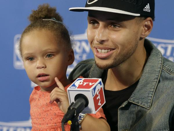 Golden State Warriors guard Stephen Curry and his daughter Riley attend a news conference after Game 5 of the NBA Western Conference finals. Curry should be seen as a role model, pundits say.