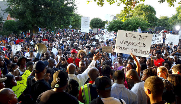 Author David Lee (center) speaks as hundreds of protesters rally in McKinney, Texas, on Monday against what they call police brutality.