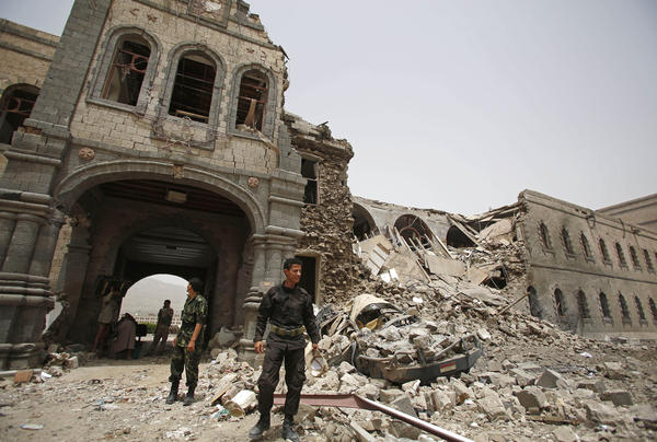 Houthi fighters stand guard in front of Yemen's Defense Ministry building in the capital Sanaa on Wednesday after it was damaged by Saudi-led airstrikes. The Houthis seized control of the capital late last year. Saudi Arabia has been bombing the Houthis since March.