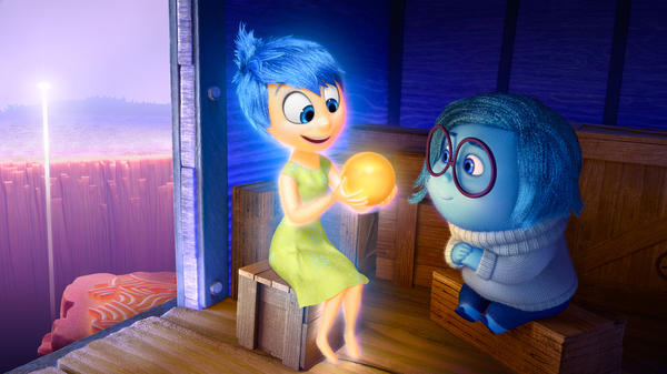 Joy (left, voiced by Amy Poehler) and Sadness (voiced by Phyllis Smith) catch a ride on the Train of Thought in Pixar's <em>Inside Out.</em> The movie opens in theaters nationwide June 19.