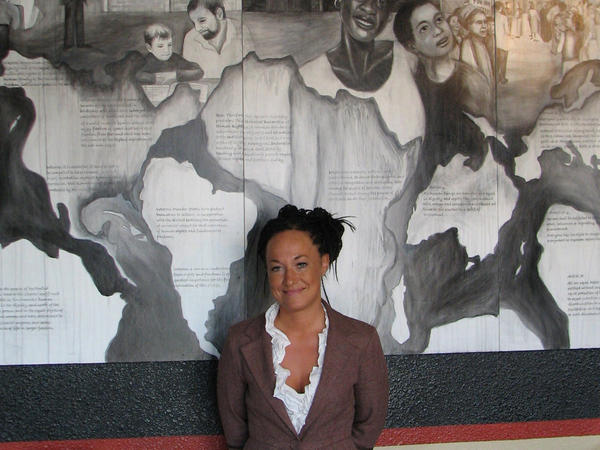 In this July 24, 2009, photo, Rachel Dolezal, a leader of the Human Rights Education Institute, stands in front of a mural she painted at the institute's offices in Coeur d'Alene, Idaho.