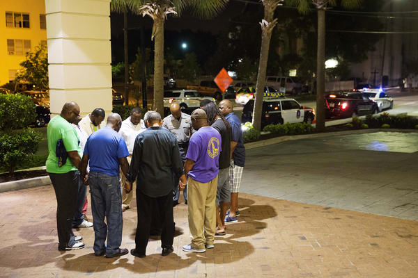 Worshippers gather to pray in a hotel parking lot across the street from the scene of the shooting.