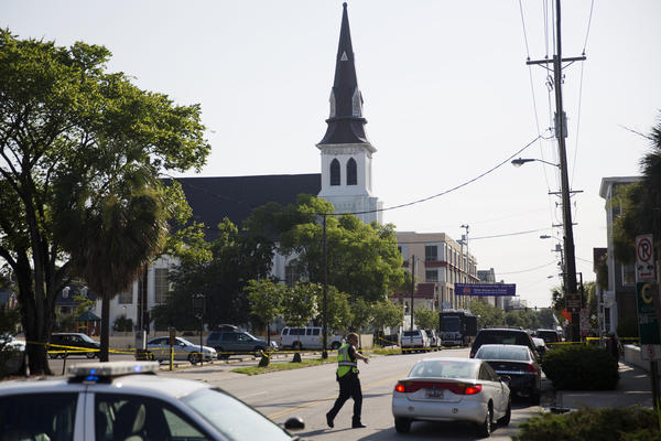 The steeple of Emanuel AME Church in Charleston, S.C., rises above the street as a police officer tells a car to move on Thursday as the area is closed off following Wednesday's shooting.
