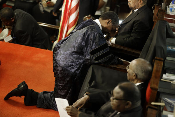 The Rev. Norvel Goff (right) prays at the empty seat of the Rev. Clementa Pinckney at the Emanuel A.M.E. Church on Sunday.