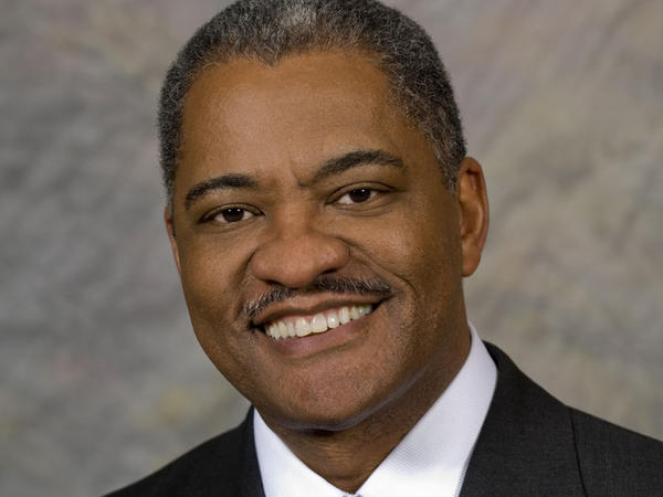 Elson Floyd's publicity shot featured his Washington State University lapel pin and a tie with WSU crimson.