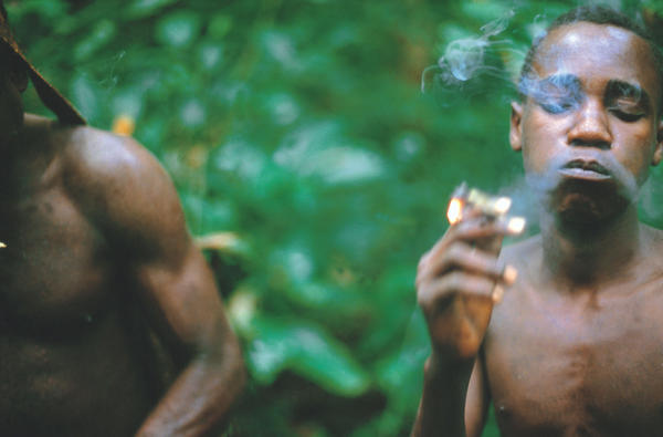 An Aka man smokes hemp while hunting in the Central African Republic.