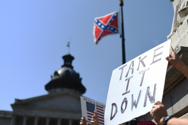 Protesters hold a sign Tuesday during a rally to take down the Confederate flag at the South Carolina Statehouse in Columbia.