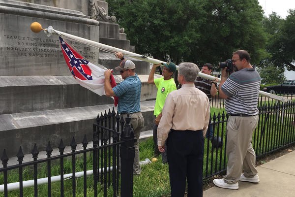 State workers take down a Confederate national flag on the grounds of the state Capitol on Wednesday in Montgomery, Ala.