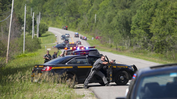 Law enforcement personnel take cover Friday afternoon after cornering two escaped prisoners off of Route 30 in Malone, N.Y. One prisoner, Richard Matt, was shot dead by law enforcement. Authorities were still searching for escapee David Sweat late Friday night.