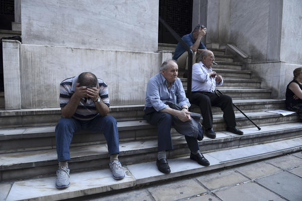 Pensioners, who usually get their payments at the end of the month, wait outside a closed bank in Thessaloniki, Greece, on Monday. Greece's government announced capital controls, and the country's banks remained closed Monday.