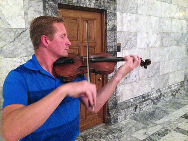 Republican State Representative Vincent Buys plays his violin late Friday night in the Capitol. He decided to play after seeing on Twitter that reporters and others were camped out waiting to see if a budget deal would be announced.
