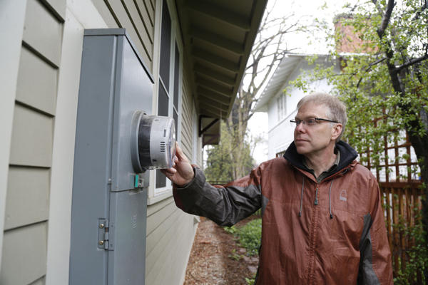 John Phelan with Fort Collins Utilities inspects the smart meter at his home. (Dan Boyce)