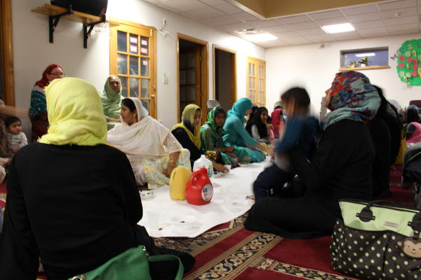 On the second floor of the mosque, women break their fast with dates, grapes, watermelon, and water.