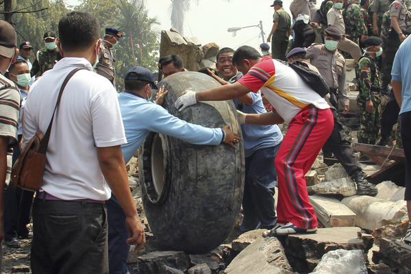Military personnel remove an aircraft wheel at the site where an air force cargo plane crashed in Medan, Indonesia, on Tuesday.