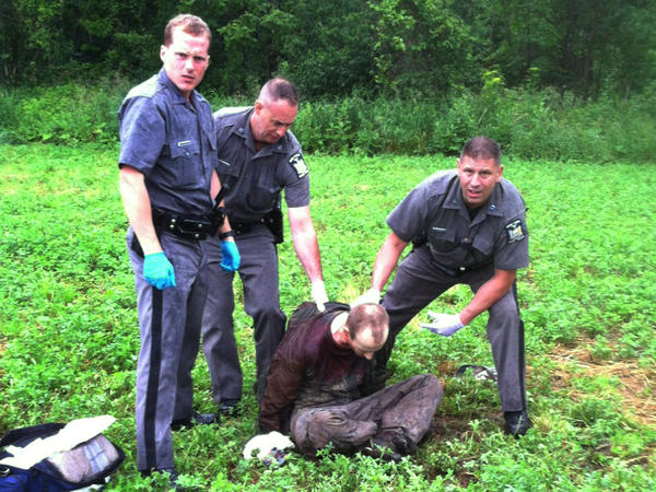 Police stand over David Sweat after he was shot and captured on Sunday. Authorities say he has told them he and Richard Matt performed a dry run of their escape the day before they broke out.