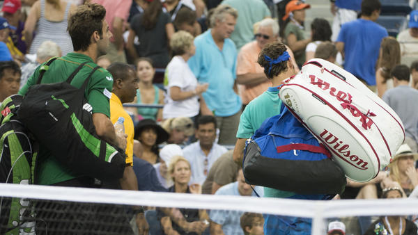 Marcel Granollers (left) and Roger Federer leave the court at the U.S. Open in Flushing, N.Y., last August. Commentator Frank Deford says with all that baggage, tennis needs caddies.