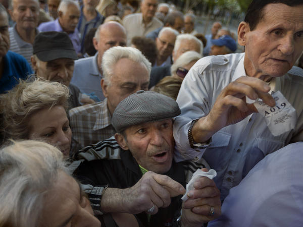 Pensioners holding their queue numbers try to enter a bank in Athens. The government ordered about 1,000 bank branches around the country to reopen Wednesday to help desperate pensioners without ATM cards cash up to $134 from their retirement checks.