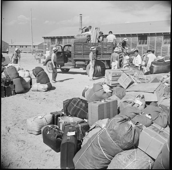 Baggage, belonging to incarcerees arriving from an assembly center at Puyallup, Washington, is sorted and trucked to barracks at the Minidoka internment camp in 1942.