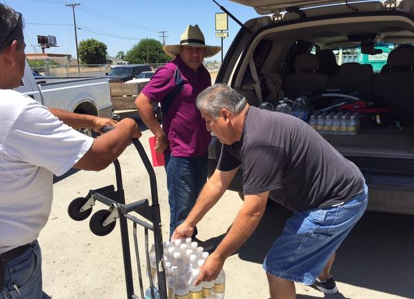 Pastor Frank Olmedo of the Spanish Church of the Nazarene in Porterville Calif., loads cases of bottled water into Humberto Hernandez's Suburban. These aid stations are a lifeline here, where residents like Hernandez have been living without water for more than six months.