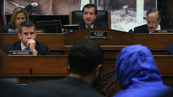 "Rep. Ed Royce (center), R-Calif., speaks during a July 2014 hearing of the House Foreign Affairs Committee, with ""Caesar,"" a Syrian army defector who wore a blue, hooded jacket to protect his identity. Caesar smuggled out of Syria more than 55,000 photographs that document the torture and killings in Syrian prisons."
