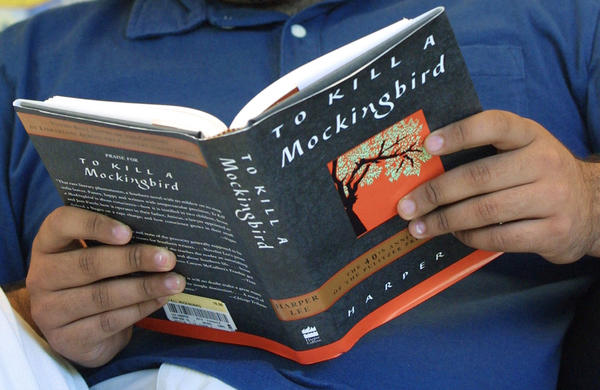 Luis Banuelos reads a copy of the 40th anniversary edition of Harper Lee's Pulitzer Prize winning novel 'To Kill A Mockingbird' September 10, 2001 at a Borders Books and Music store in Chicago. (Tim Boyle/Getty Images)