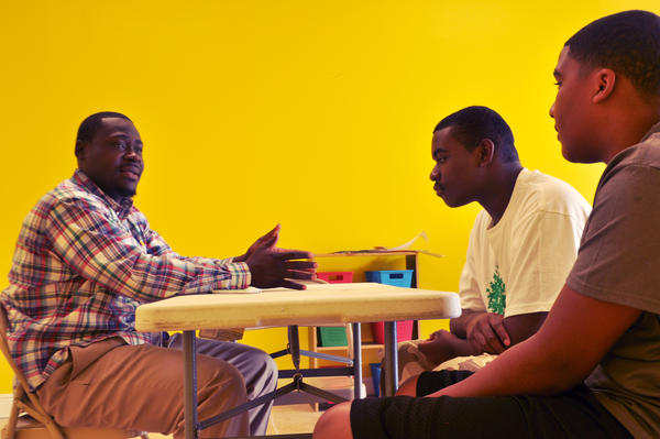 Charles Williams, co-director of Miami's Generational Cure mentoring program, talks about safe sex with Traivon Harris, left, and Dwayne Jackson, right.