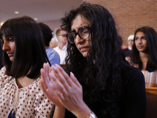 Yusra Siddiqui, right, and Zoha Ahmad, who came with others from the Islamic Society of Greater Chattanooga to offer their support, pray during an interfaith vigil at Olivet Baptist Church held in remembrance of victims of Thursdays shootings.