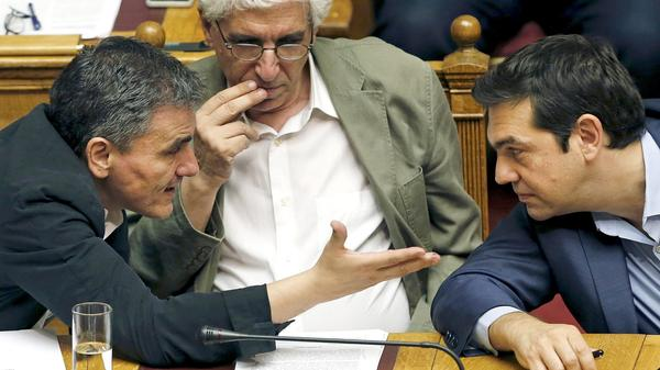 Greek Prime Minister Alexis Tsipras listens to Finance Minister Euclid Tsakalotos as Justice Minister Nikos Paraskevopoulos looks on during a parliamentary session in Athens on Thursday.