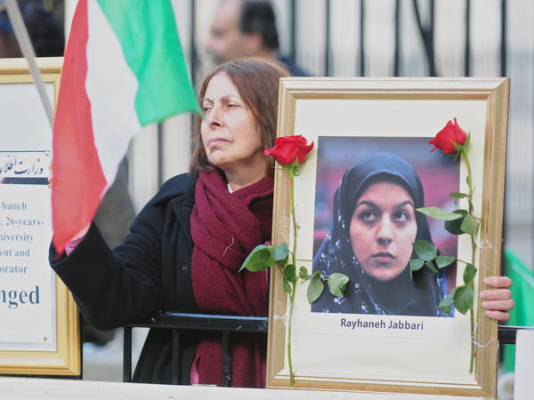 """People gather opposite Downing Street during a protest against the execution of a young woman in Iran, in October of last year. Amnesty International says that Iran has undergone an """"unprecedented spike"""" in executions in recent months."""