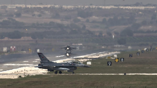 A U.S. Air Force plane takes off as a Turkish air force fighter jet taxis at the Incirlik airbase, southern Turkey, in 2013. Reversing an earlier policy, Ankara has agreed to allow the U.S.-led coalition to fly anti-ISIS airstrikes from the base.
