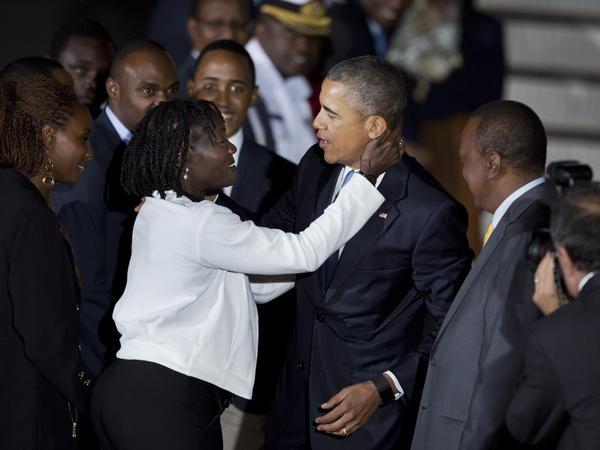 President Obama is hugged by his half-sister, Auma Obama, accompanied by Kenya's President Uhuru Kenyatta (right) as he arrives at the Jomo Kenyatta International Airport in Nairobi on Friday.