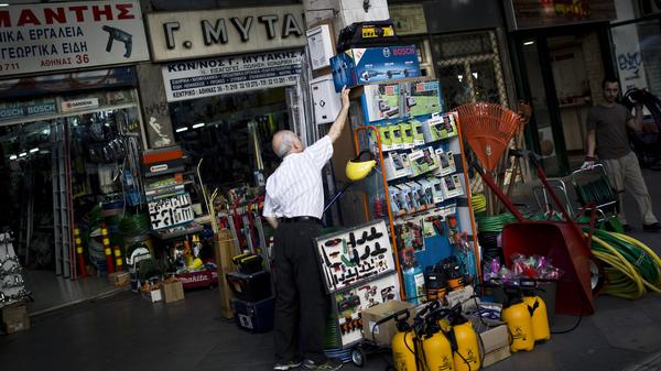 A shop owner arranges his goods in central Athens on Monday. Greek banks have reopened, but capital controls remain in place.