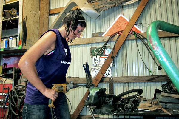 Shelby Miller tools on a part for a car for the derby. Miller comes from a derby family — her mother, father, and brother all participate.