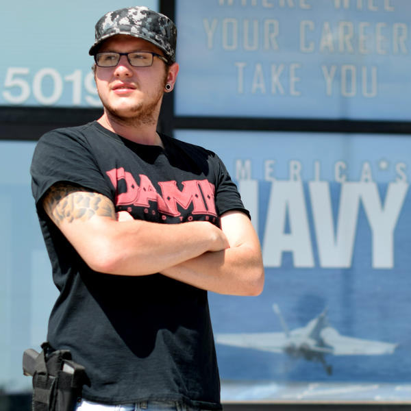 "Zachary Gallegos, 23, stands guard outside the Armed Services Recruiting Center on Thursday in Sioux Falls, South Dakota. The Pentagon has asked such self-appointed ""armed citizens"" to leave, citing security concerns."