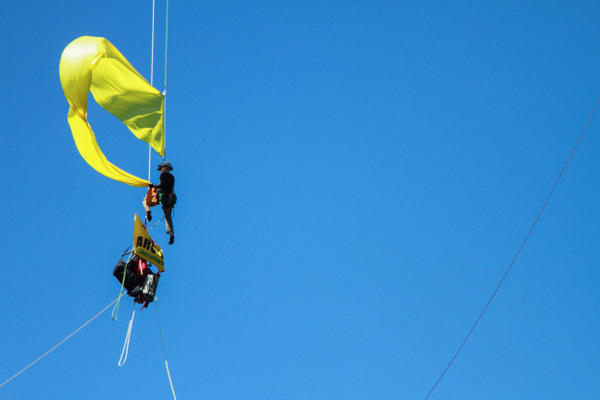 <p>A protester releases a flag that was lowered down from the St. Johns Bridge Wednesday, July 29, 2015. Protesters hung from the bridge in protest to block a Shell icebreaker which was scheduled to return to Alaska.</p>