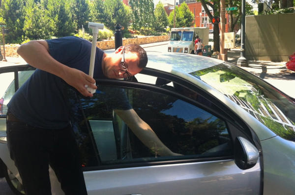 <p>Portland State University researcher Jackson Voelkel attaches a thermometer to a car window.</p>