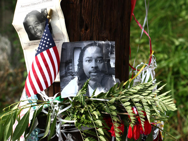 Photos of Samuel DuBose hang on a pole at a memorial on Wednesday in Cincinnati near where he was shot and killed by a University of Cincinnati police officer.