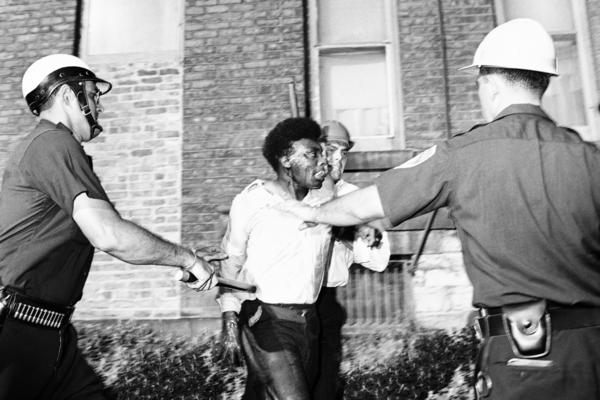 Police officers struggle with a man dripping wet from the blast of a fire hose during rioting in Rochester, N.Y., in 1964.