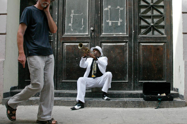 Tourists mill past a trumpet player in the restored part of Old Havana.