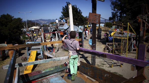 A boy paints the railings of a wooden fort at the Berkeley Adventure Playground. Nails, hammers and buckets of paint are just part of the fun.