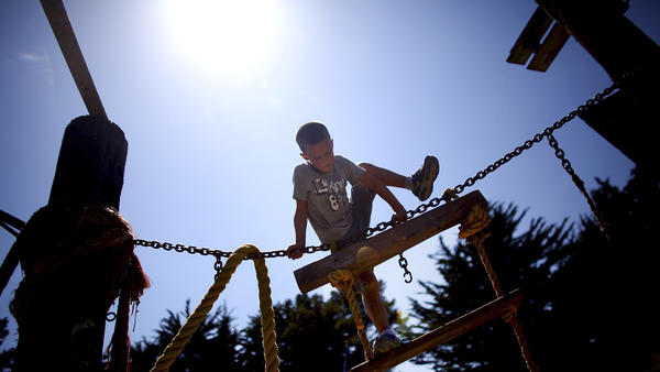 Seven-year-old Tyler Swenson uses a rope and a ladder to climb a wooden structure at the Berkeley Adventure Playground in California.