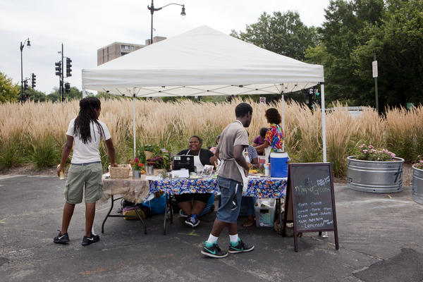 Students from Eastern Senior High School in Washington, D.C., sell vegetables, soaps and salts at the Aya farmers market on July 25.