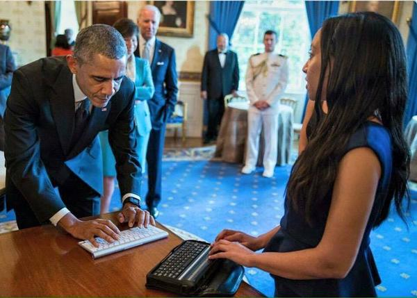 Using a digital device that displays Braille characters, Haben Girma talks with President Obama at a White House ceremony marking the 25th anniversary of the Americans with Disabilities Act.