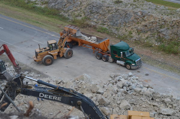 A front-end loader places debris into a truck parked along I-35 that will haul the rocks to a nearby quarry.