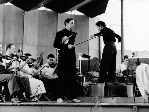 Totenberg holds his Stradivarius before a rehearsal in Aspen, Colo., in the late 1950s. Izler Solomon (right) conducts the orchestra.